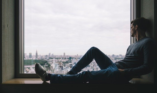 muž sedí v okně